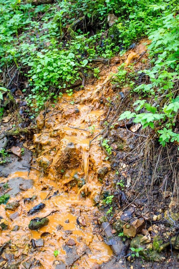 Bruine vloeibare afvoerkanalen in een ravijn stock foto