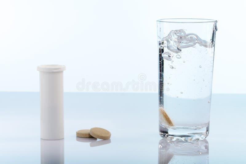 Bruisende pillen op het glas water royalty-vrije stock foto's
