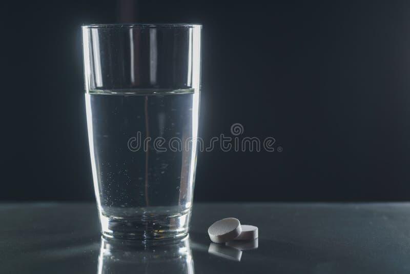 Bruisende tablet in water met bellen stock afbeelding