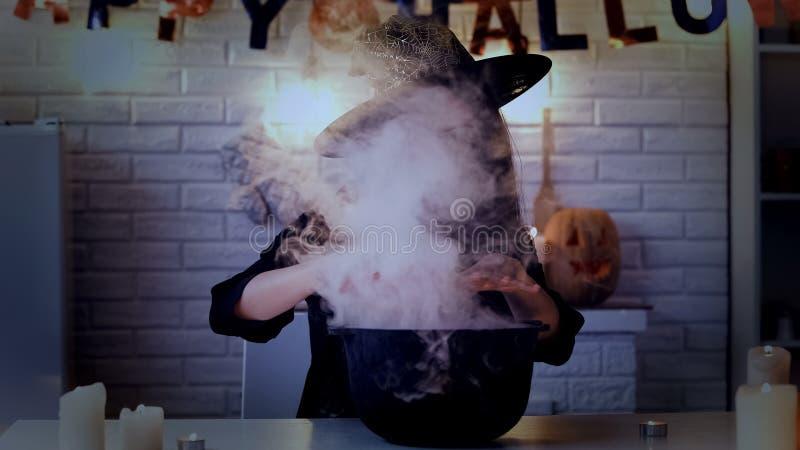 Bruja asustadiza que hace pociones mágicas en su pote con el humo blanco, víspera de Halloween fotografía de archivo