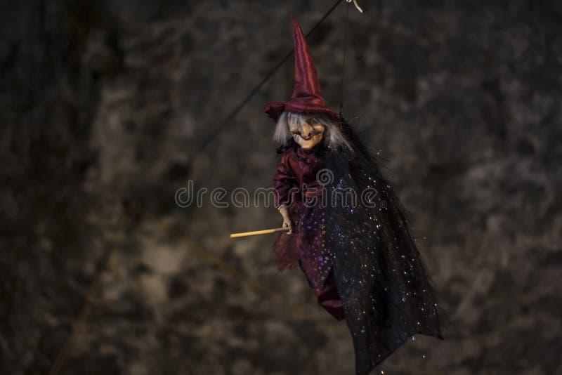 Bruja con el palo de escoba y el sombrero que cuelgan en el techo Decoraci?n a V?spera de Todos los Santos fotografía de archivo