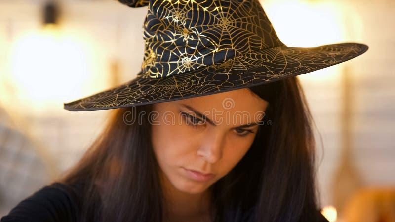 Bruja concentrada en sombrero que conjura, magia negra, partido de Halloween del traje foto de archivo