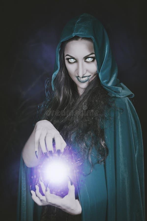 Bruja de Halloween con la bola de fuego en sus manos imagenes de archivo