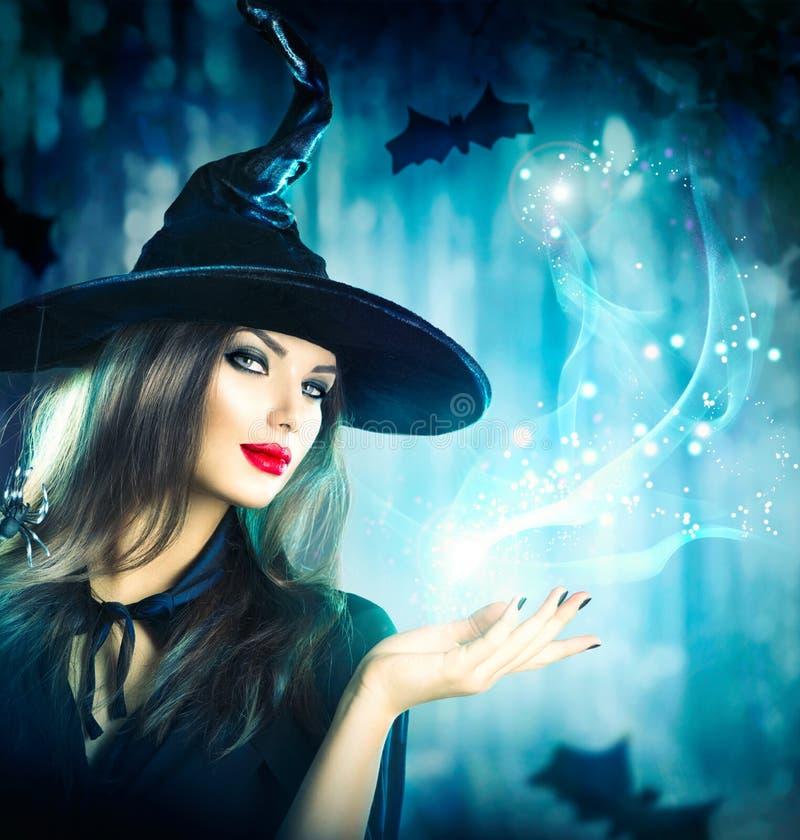 Bruja de Halloween que lleva a cabo la luz mágica fotos de archivo