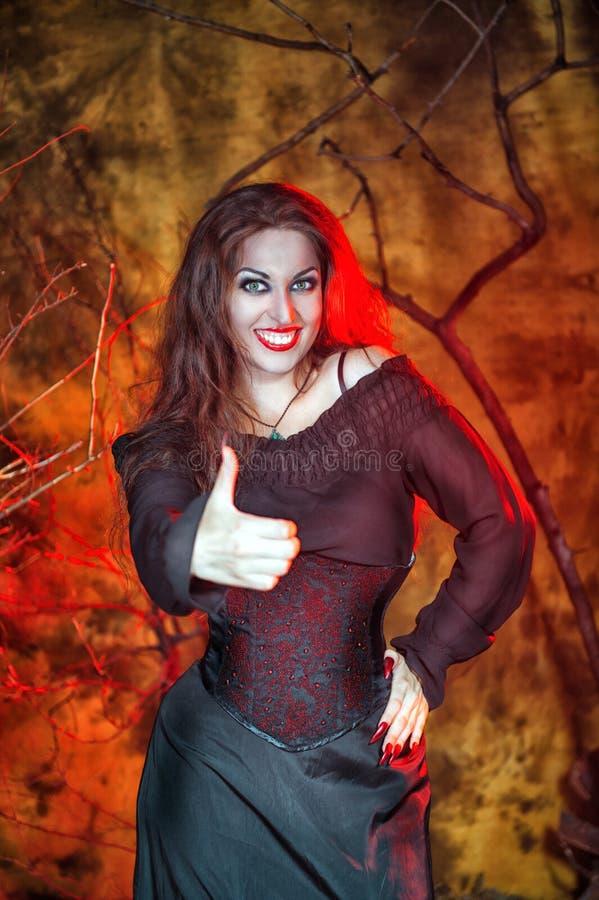 Bruja de Halloween que muestra los pulgares para arriba fotos de archivo
