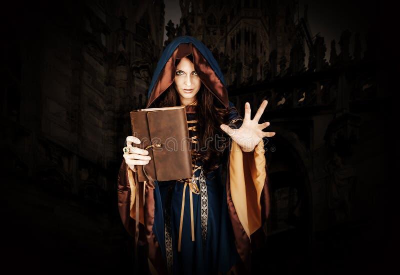 Bruja de Halloween que sostiene el libro mágico de los encantos que hacen magia fotos de archivo