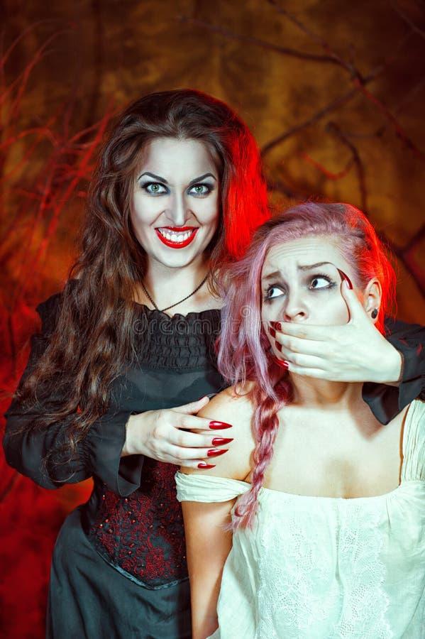 Bruja de Halloween y su víctima imagen de archivo