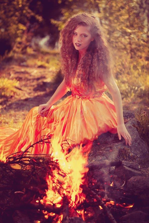 Bruja de la belleza en el bosque cerca del fuego Mujer mágica que celebra fotos de archivo libres de regalías