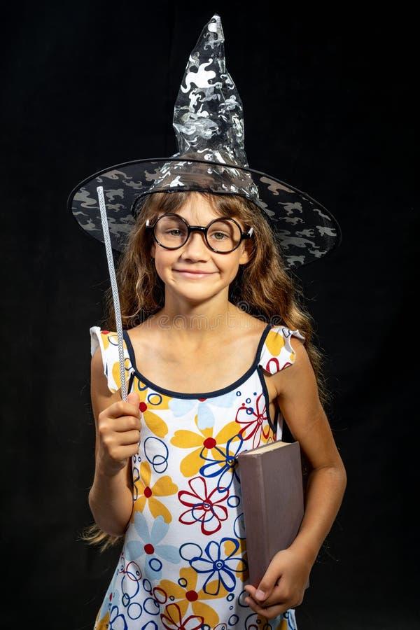 Bruja de la muchacha, con un libro y una vara mágica, en un sombrero, en un fondo negro foto de archivo