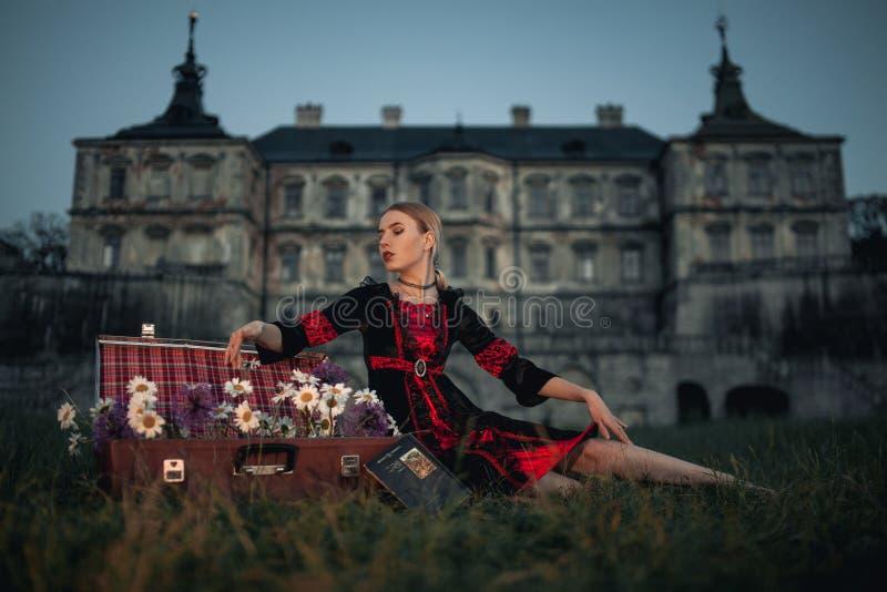 Bruja de la mujer al lado de la maleta con las flores en fondo del castillo antiguo foto de archivo