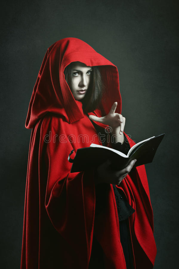 Bruja encapuchada rojo oscuro que lee un libro fotografía de archivo libre de regalías