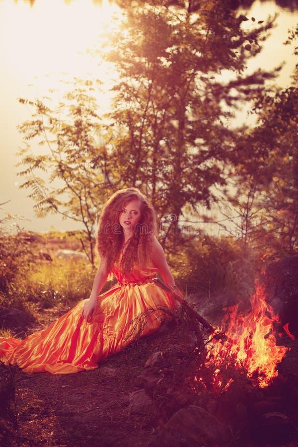 Bruja hermosa en el bosque cerca del fuego Celebrat mágico de la mujer foto de archivo