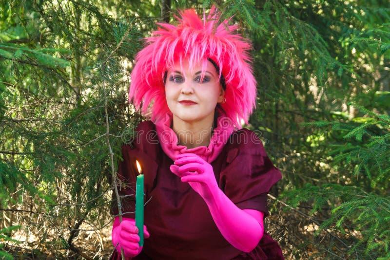 Bruja joven en ropa púrpura con una vela en su mano en el bosque imágenes de archivo libres de regalías