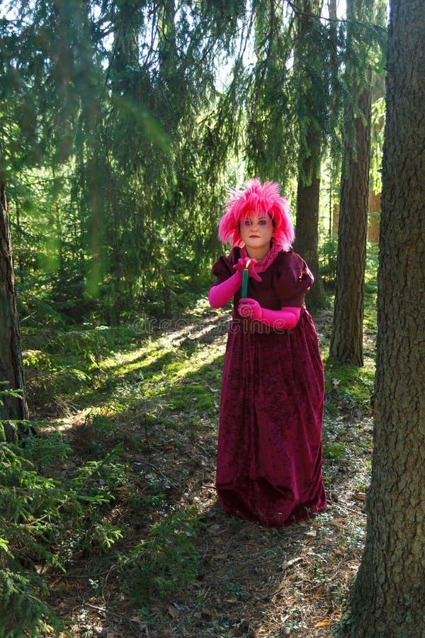 Bruja joven en ropa p?rpura en el bosque con una vela en su mano imágenes de archivo libres de regalías