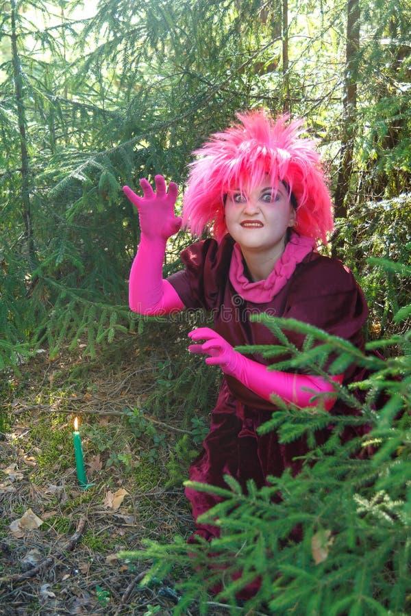 Bruja joven en ropa p?rpura en el bosque con una vela en su mano foto de archivo libre de regalías