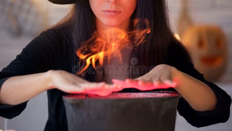 Bruja joven en vestido negro que conjura y que cocina la poción, magia de la víspera de Halloween foto de archivo