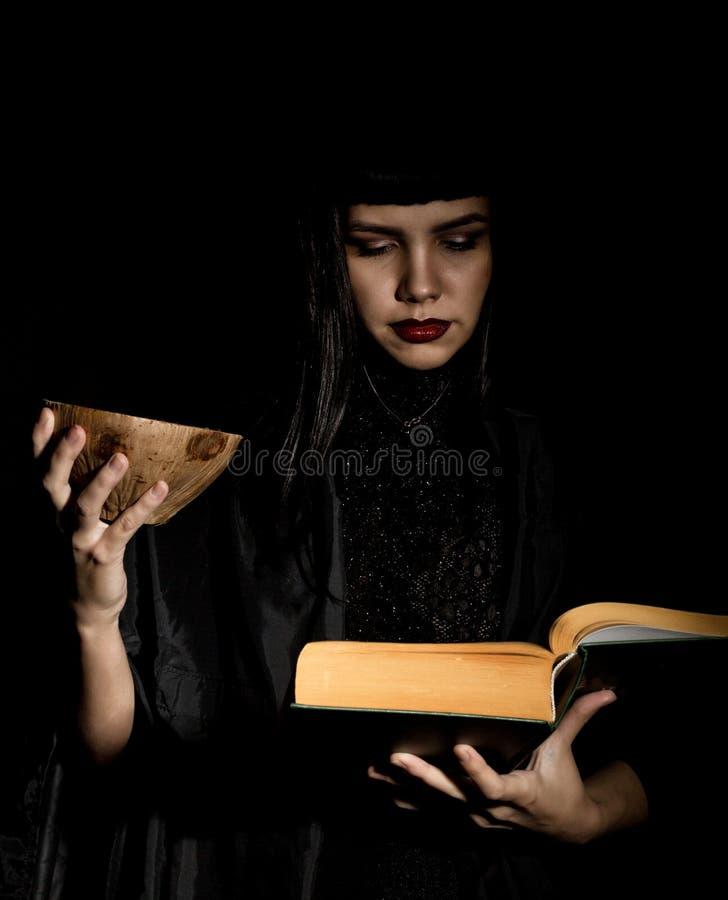 Bruja joven hermosa con un libro de encantos fotos de archivo