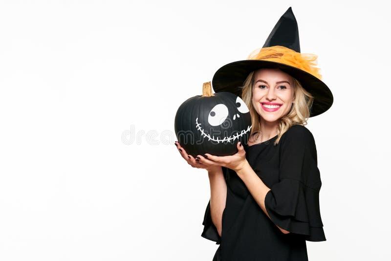 Bruja sonriente magnífica de Halloween que sostiene una linterna de Jack o Mujer joven hermosa en las brujas sombrero y traje que foto de archivo