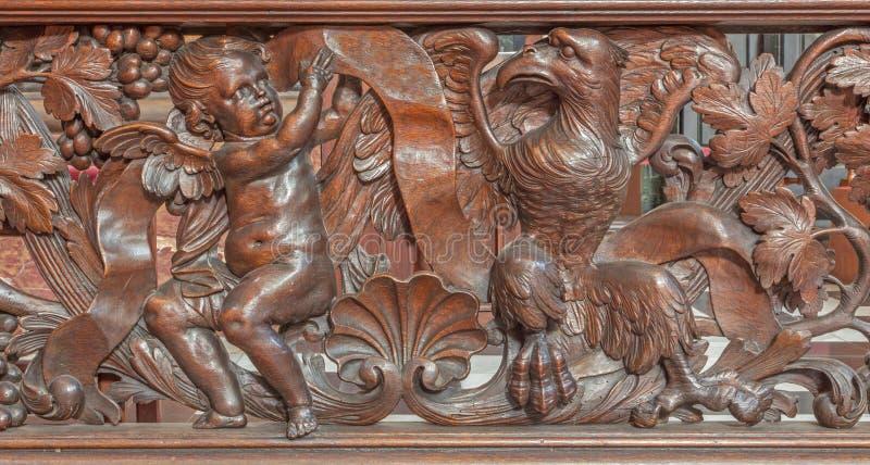 Brujas - alivio tallado del ángel y del águila como evangelista St Matthew y San Juan en Karmelietenkerk (iglesia de Carmelites) foto de archivo libre de regalías