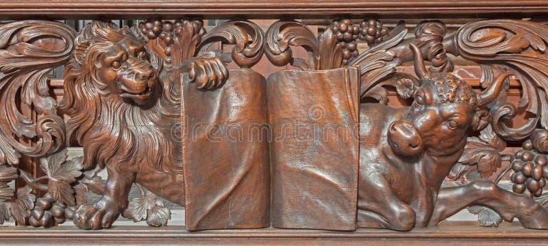 Brujas - alivio tallado del león y del toro como evangelista St Mark y St Luke en Karmelietenkerk (iglesia de Carmelites) imágenes de archivo libres de regalías