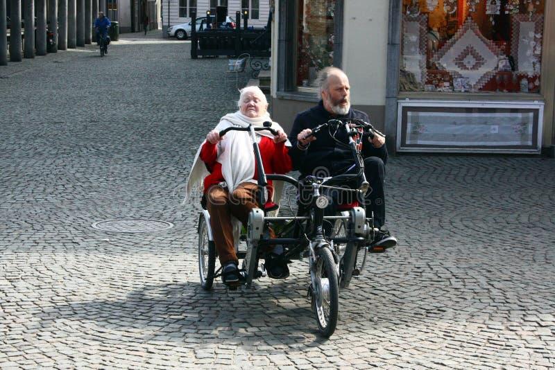 BRUJAS, BÉLGICA 03 26 2018 turistas mayores de los pares montan una bicicleta de lado a lado en tándem fotos de archivo