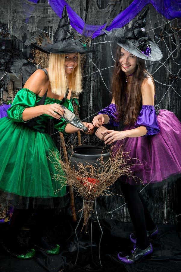 Brujas con el pote para la presentación de las pociones fotografía de archivo