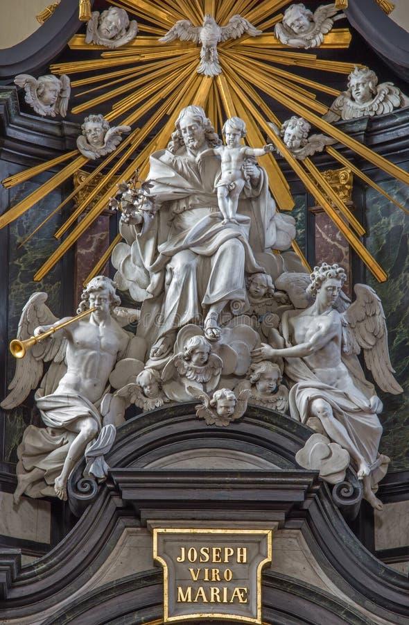 Brujas - la estatua tallada de San José con el niño y el angesl en el altar principal en Karmelietenkerk fotografía de archivo libre de regalías
