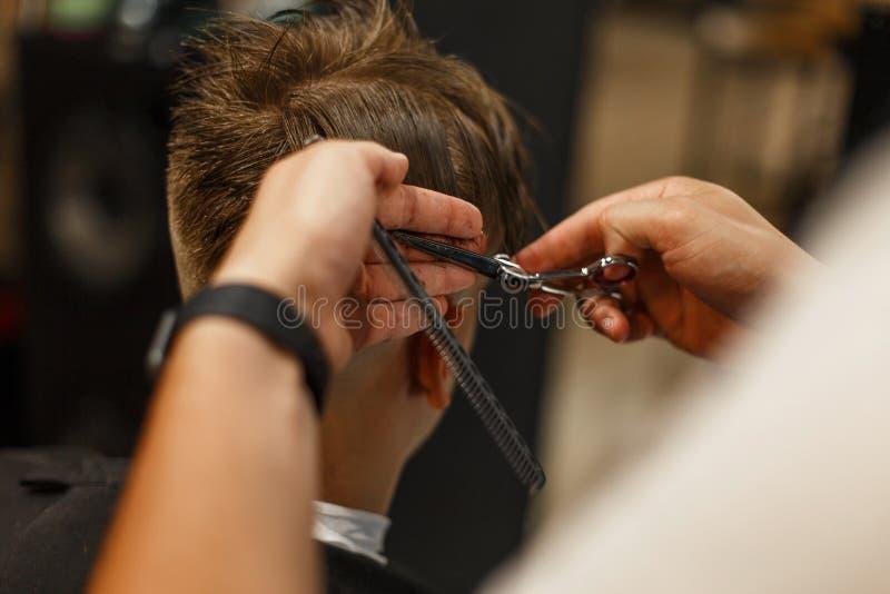 Bruk av hårtorken Yrkesmässig frisör som gör frisyren royaltyfri bild