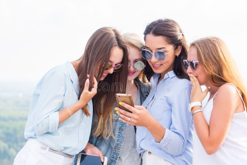 Bruk av smartphones, internet, applikationer och meddelanden En grupp av härliga flickor ser det telefonflickvännen och skrattet royaltyfri bild