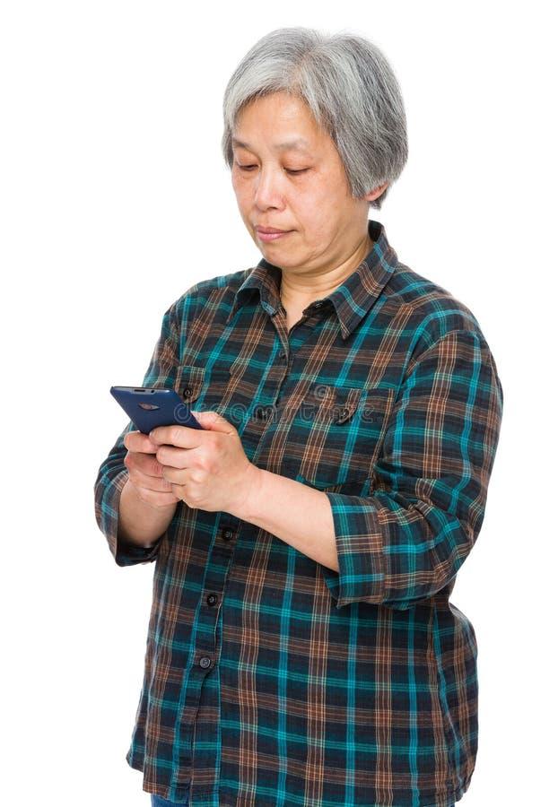 Bruk för gammal kvinna av mobiltelefonen royaltyfri bild