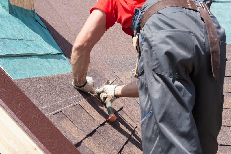 Bruk för Rooferbyggmästarearbetare som en hammare för installation av att taklägga överlappar royaltyfri foto