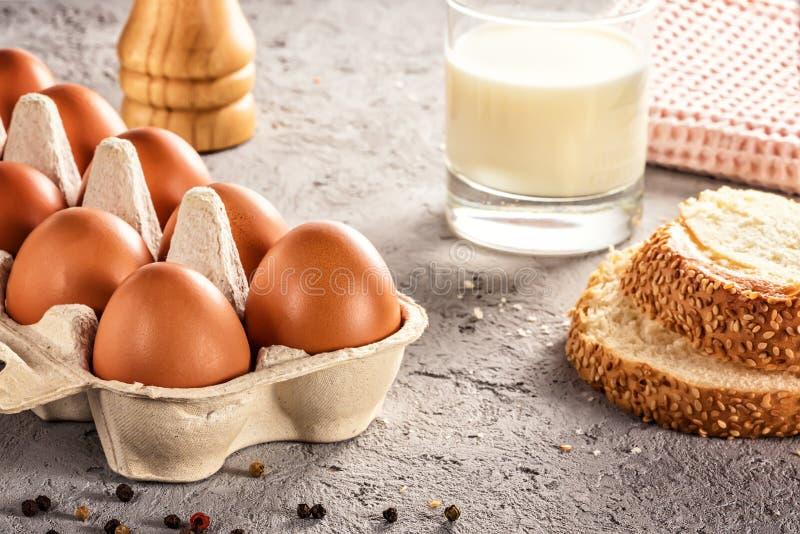 Bruka det rå nya ägget i packebröd mjölkar på ägget för ägg för grå färger tabellen förvanskade stekte omelettet royaltyfri fotografi