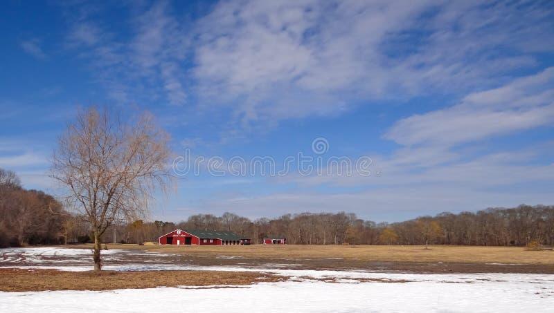 Bruka med den röda ladugården på en vinterdag royaltyfri bild