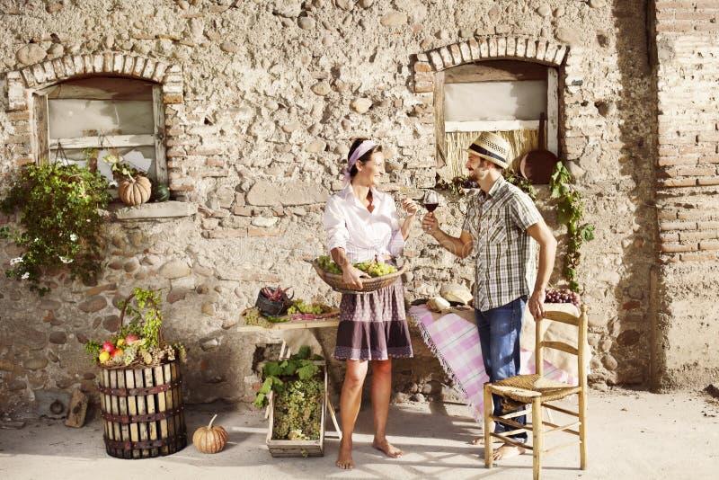Bruka par som gör ett rostat bröd med ett exponeringsglas av vin arkivbilder
