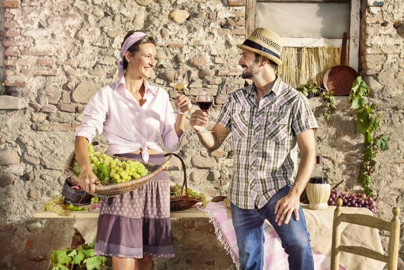 Bruka par som gör ett rostat bröd med ett exponeringsglas av vin, skördtid arkivbild