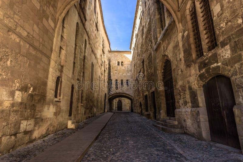 Brukowiec ulica między wysokimi murami w średniowiecznym mieście zdjęcia stock