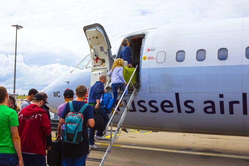 Bruksela Belgia, Czerwiec, - 19, 2016: Ludzie wsiada Brukselskiego linia lotnicza samolot Pasażerski odprowadzenie tyły zdjęcia stock