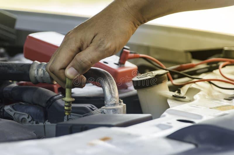 Brukshand för auto mekaniker av teknikeren som kontrollerar eller fixar motorn royaltyfria bilder
