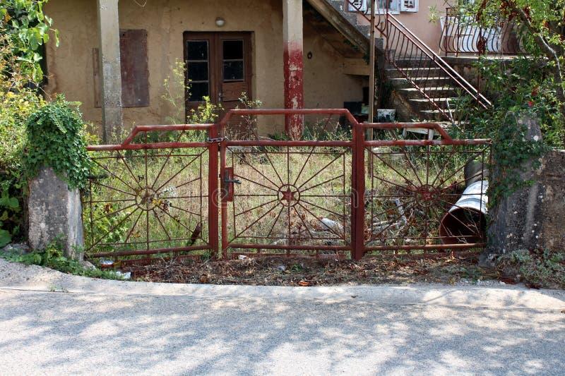Brukujący drogowy wejście zaniechany rodzina dom blokujący z metali drzwiami blokował z silny łańcuszkowy prowadzić porosły front fotografia stock