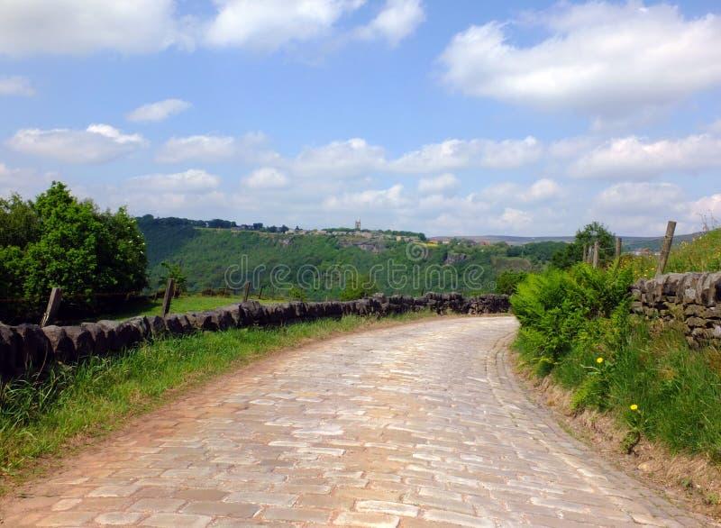 Brukuję kraju pasa ruchu wyginać się zjazdowy w odległą lesistą dolinę otaczającą suchymi kamiennymi ścianami i zieleni polami fotografia royalty free