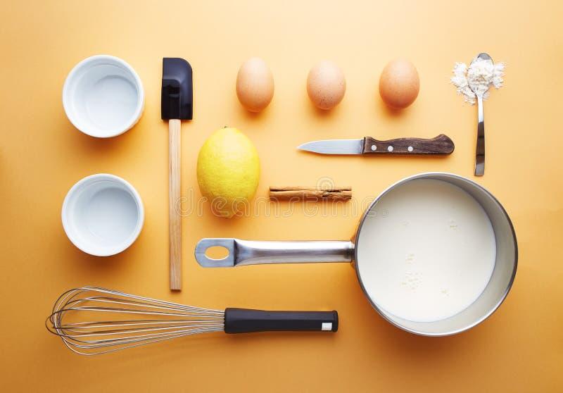 Brulee ingredienser för kräm på gul bakgrund royaltyfri foto