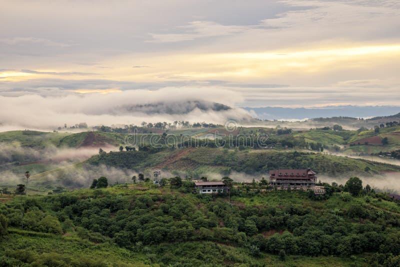 Brume blanche avec le lever de soleil tôt au-dessus de la colline et du pavillon images stock