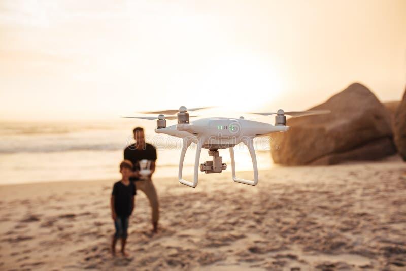 Brummen, das vom Vater und vom Sohn auf Strand laufen gelassen wird stockfotos