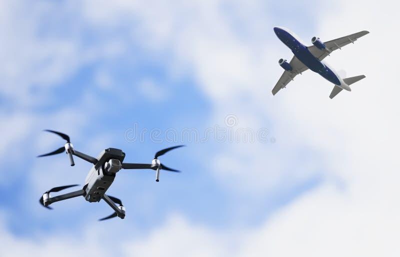 Brummen quadcopter Fliegen und Flugzeugflugzeuge im Himmel in der Gefahr des Absturzes oder des Zusammenstoßes lizenzfreie stockbilder