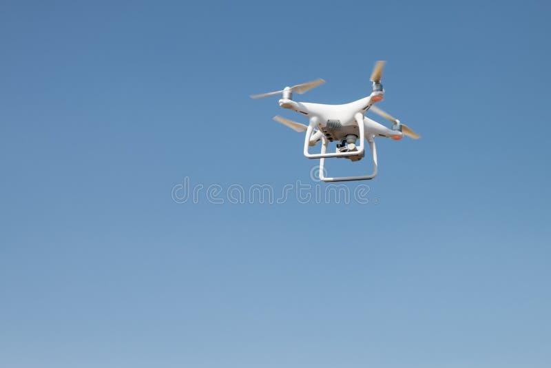 Brummen quadcopter Schwebeflug auf Himmelhintergrund stockbild