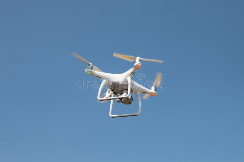 Brummen quadcopter Schwebeflug auf Himmelhintergrund, Brummenkamera, im Bauernhof lizenzfreie stockfotos
