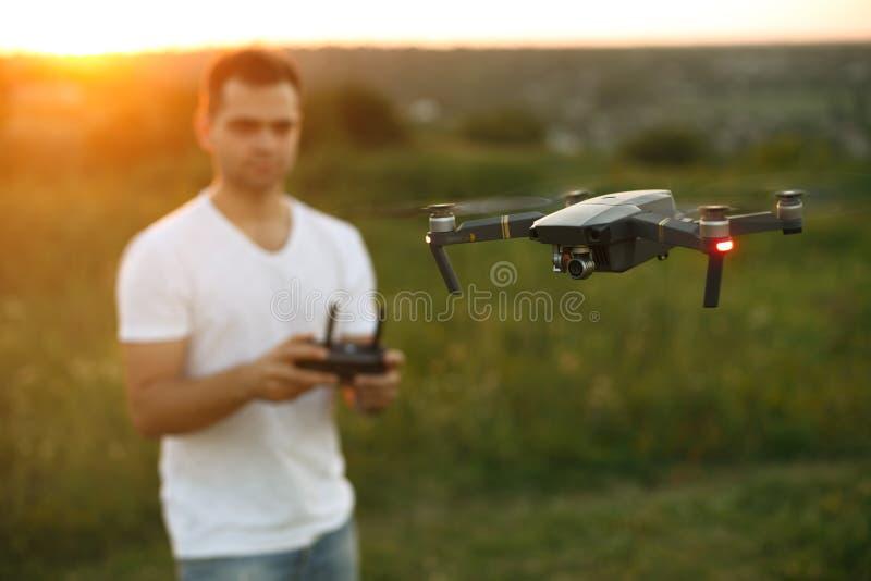 Brummen schwebt vor Mann mit Fernprüfer in seinen Händen Quadcopter fliegt nahe Piloten Kerl, der Luftfotos macht stockbild