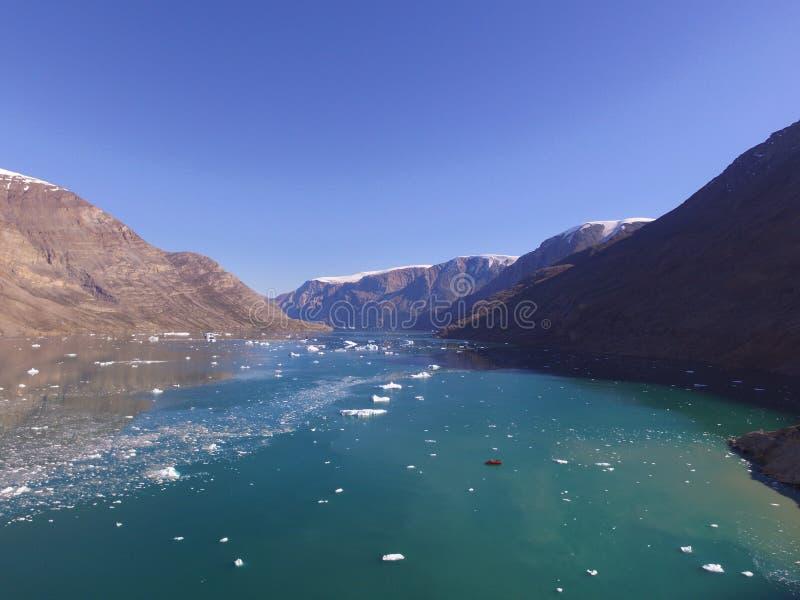 Brummenluft- Bild von Eisbergen und von trübem Glazial- Abfluss in einem schmalen Fjord in Nordost-Grönland lizenzfreie stockfotos