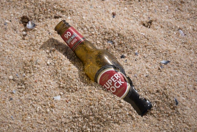 Brun ölflaska av portugisiskt öl på stranden arkivfoto