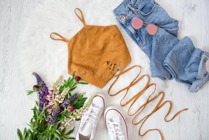 Brun överkant med band, jeans, vita gymnastikskor Bukett av löst royaltyfri foto